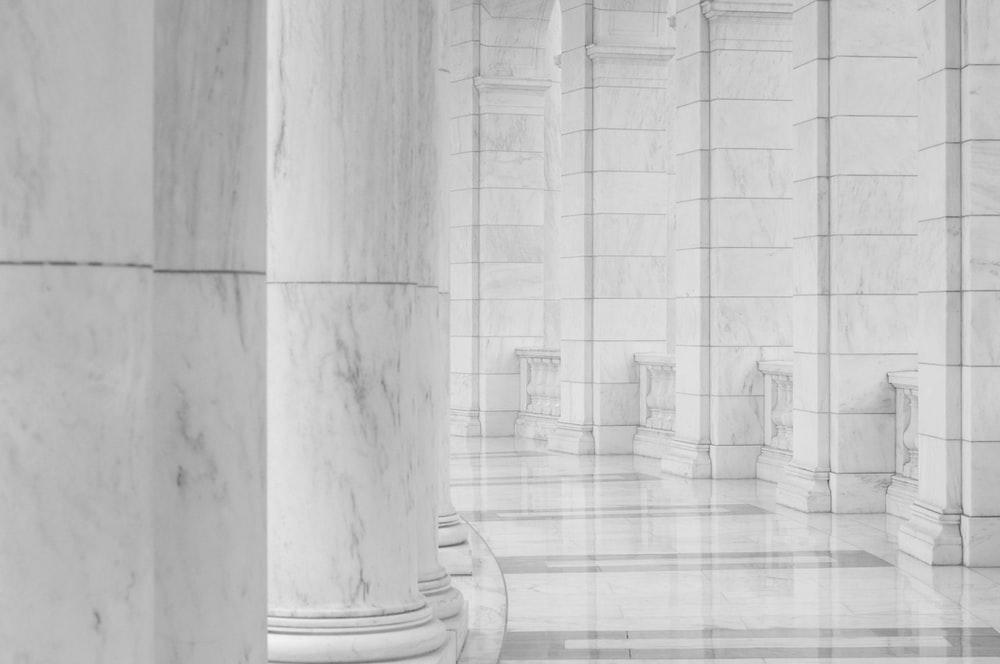 minimalist photography of hallway between columns