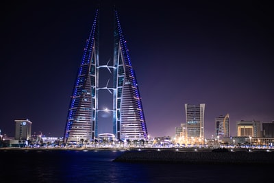 triangular-shape tower near body of water bahrain zoom background