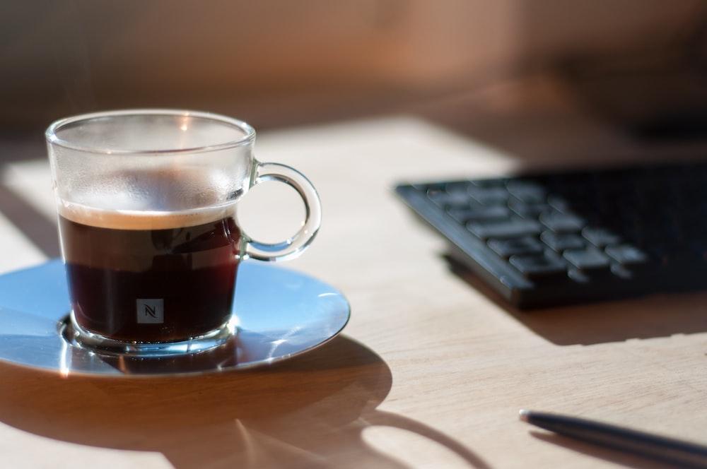 clear glass tea cup beside keyboard