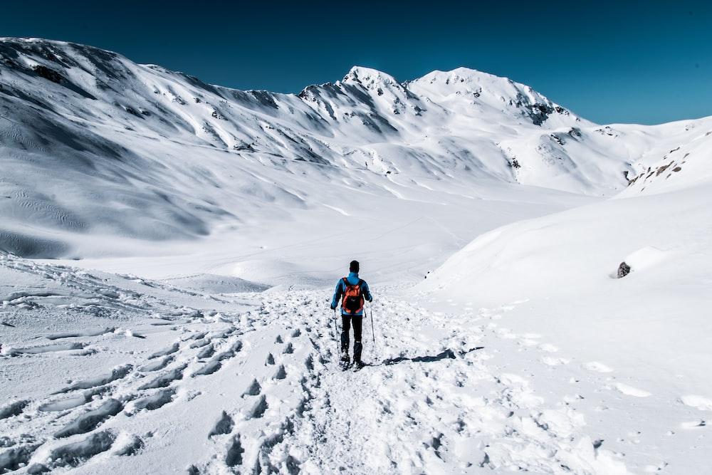 man walking on snow field near mountain