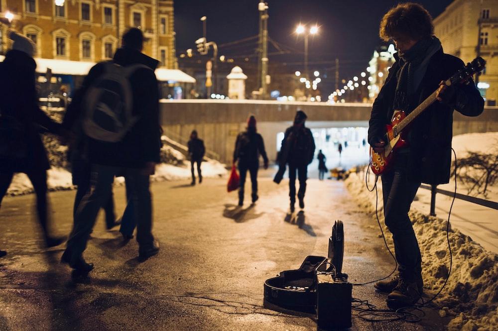 man playing guitar on street during nighttime