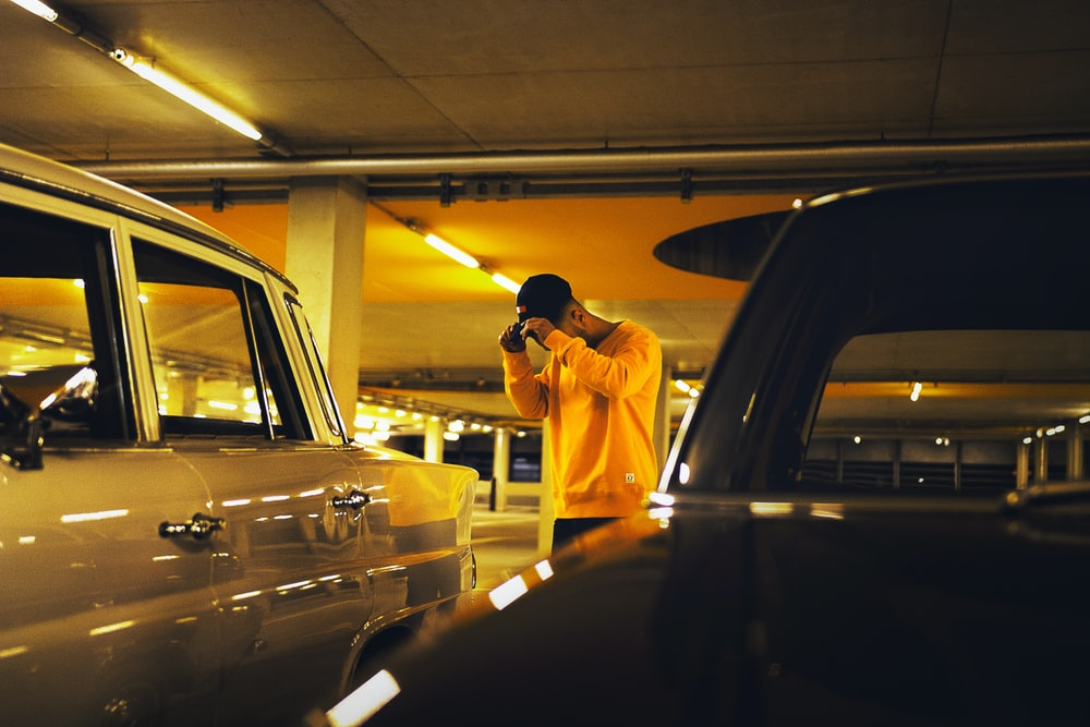 man holding cap standing between car on parking lot