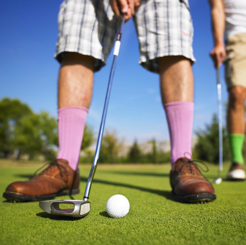low angle photo of man playing golf taken at daytime
