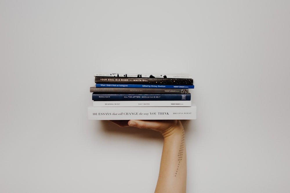 person holding pile of books