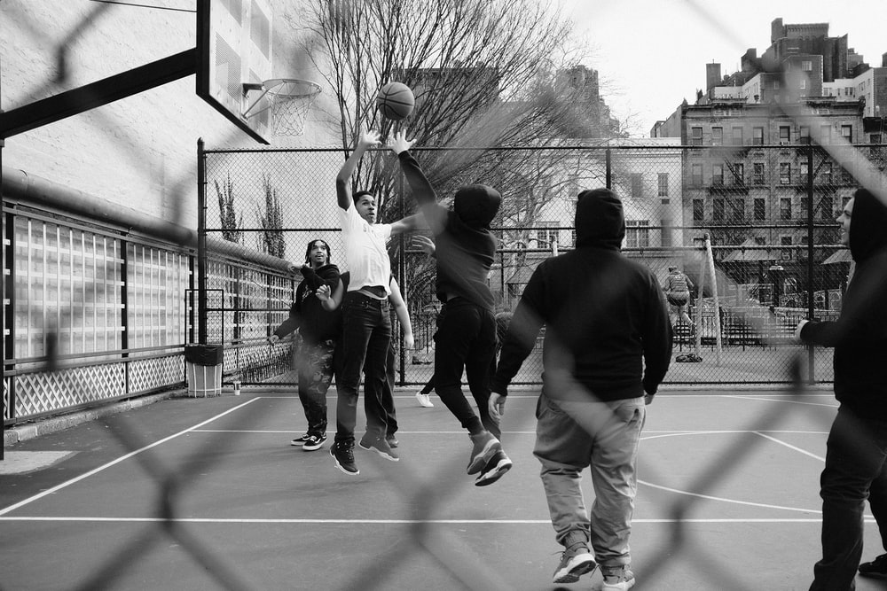 grayscale photo of group of men playing street basketball
