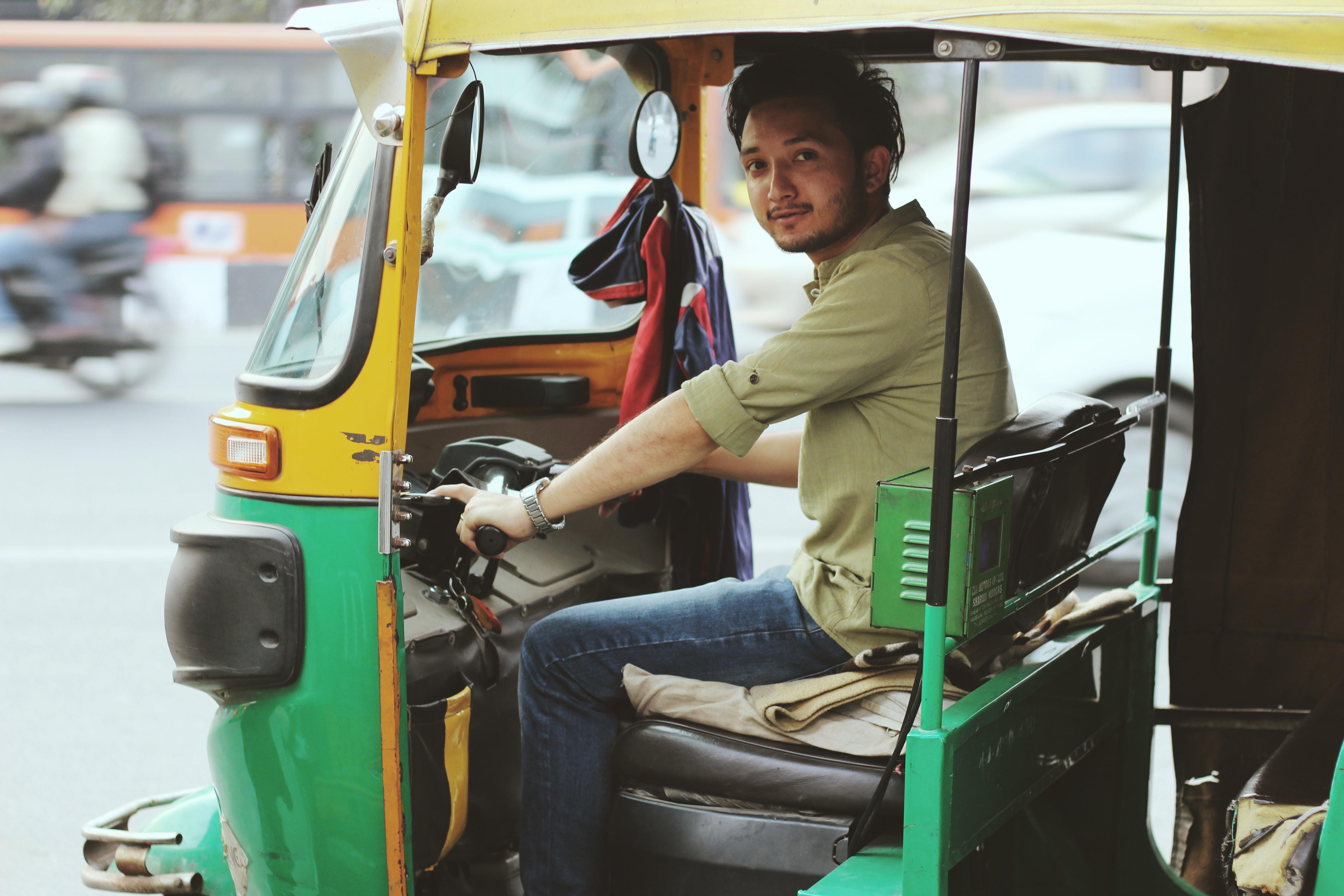 man riding on auto rickshaw