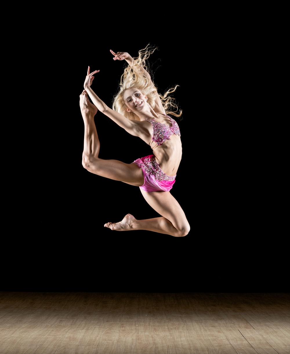 woman stretching her legs and arms in mid air