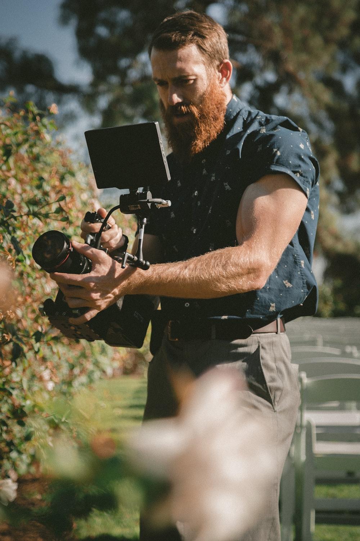 man holding camera taking photos
