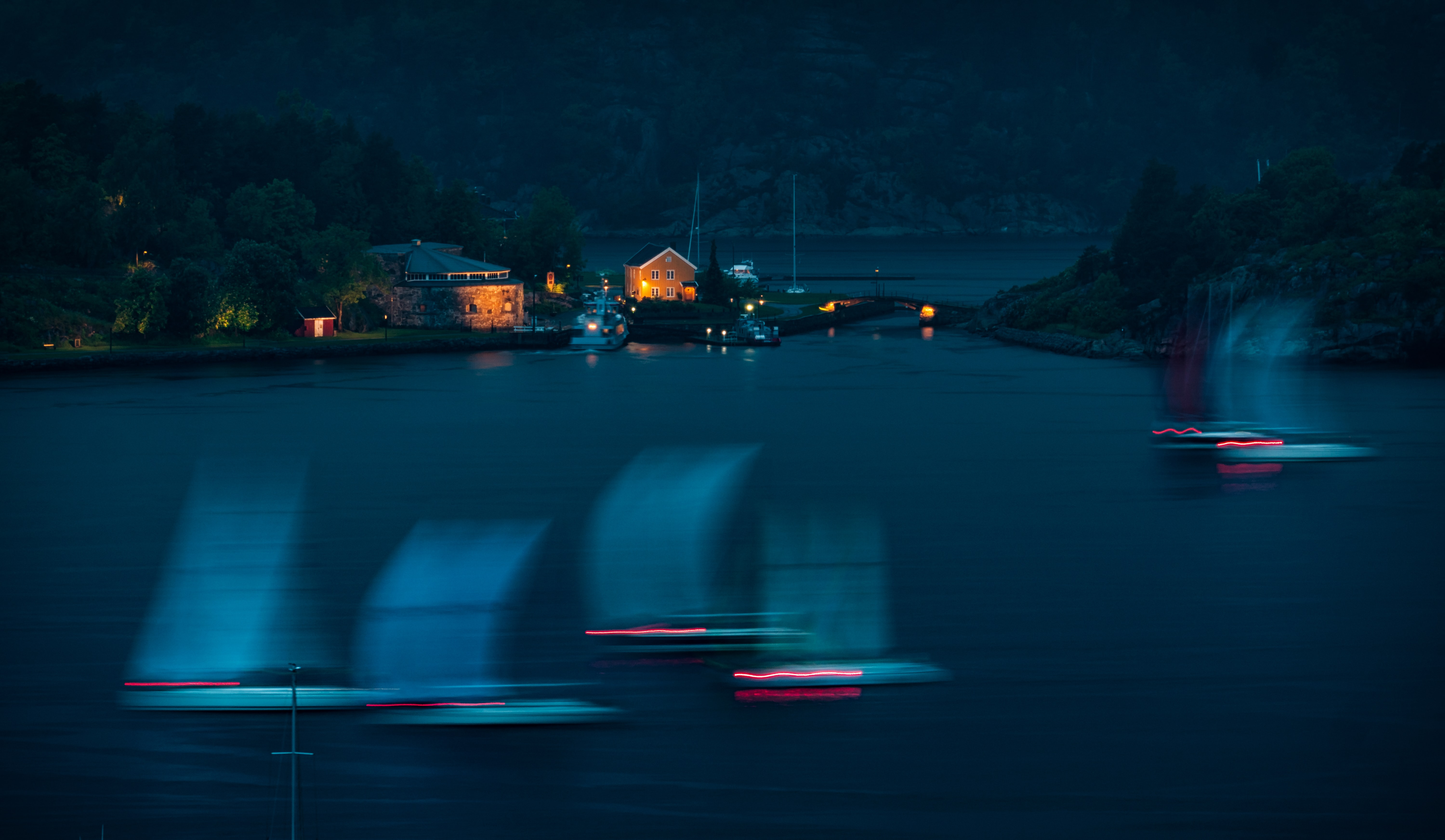 boats on body of water near lighted house