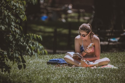 woman reading books in park