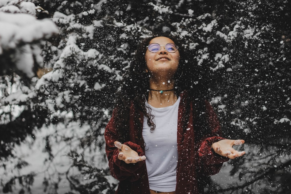 woman in white shirt touching the snow