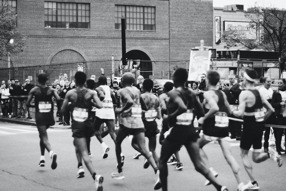 grayscale photo of men running on marathon