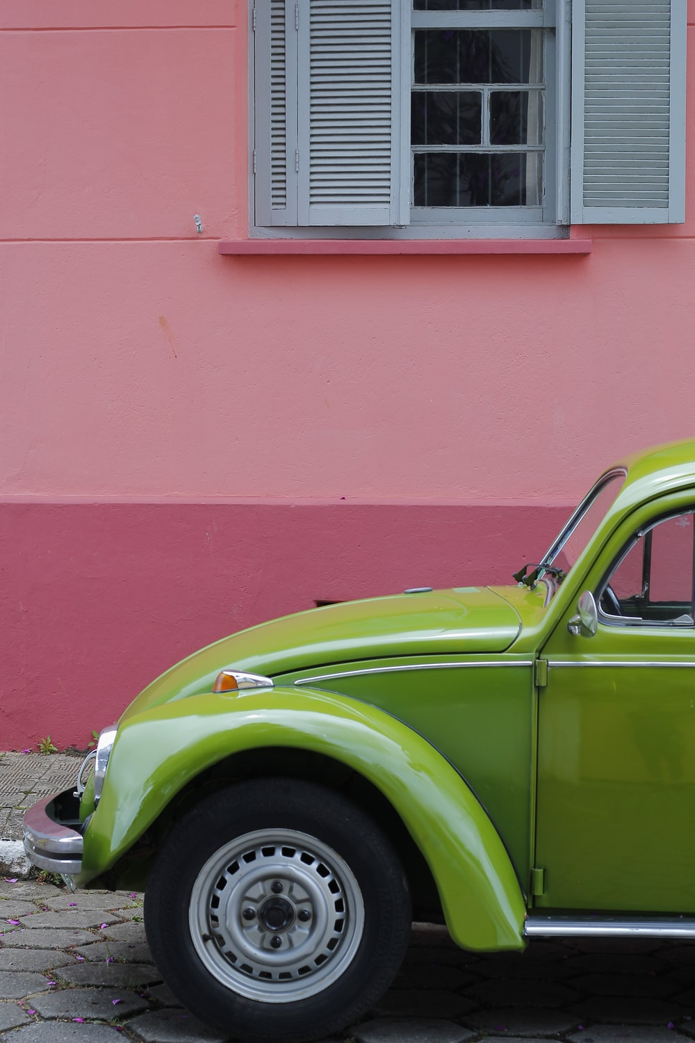 green Volkswagen beetle beside of pink building
