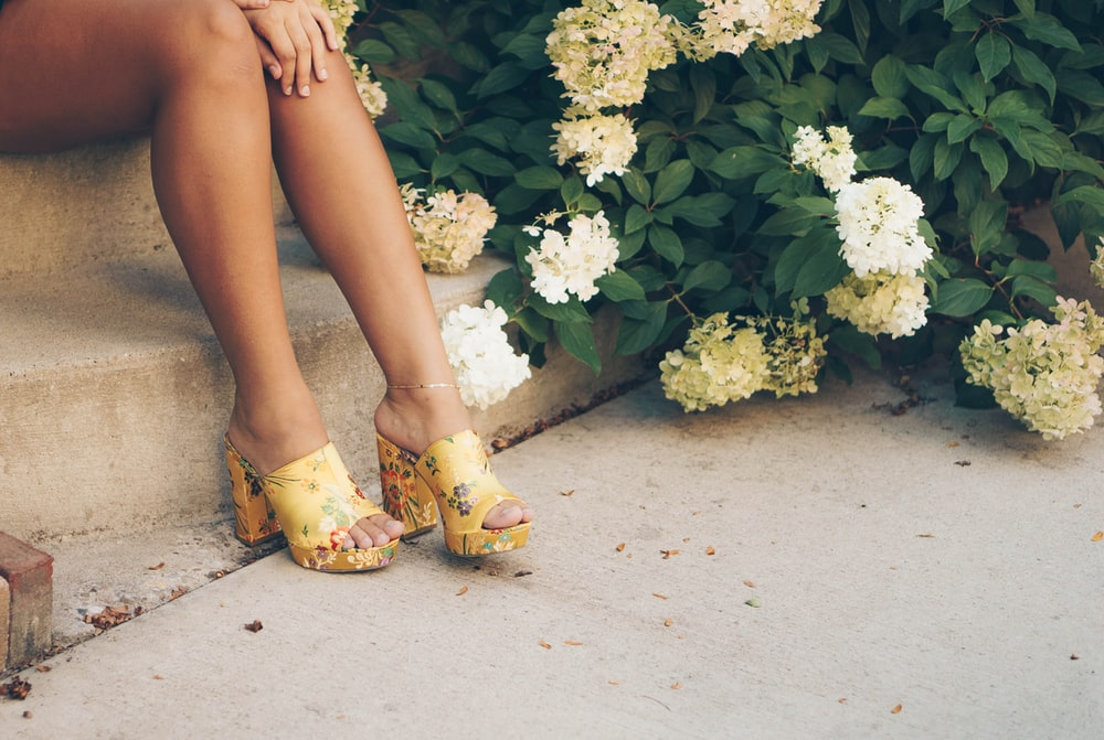 woman sitting on brown stair beside yellow and white flowers