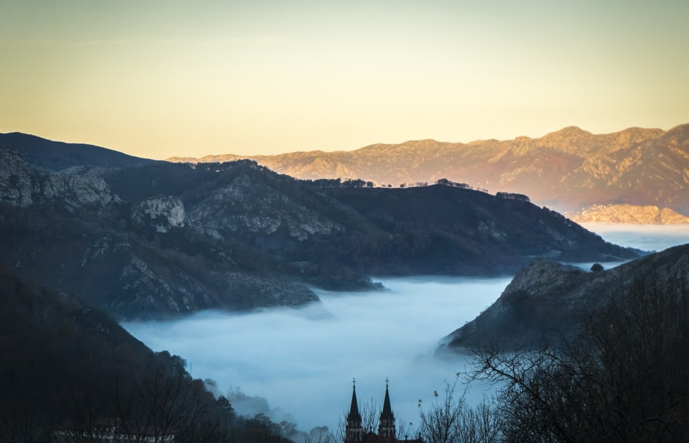 landscape photo of fogs between gray mountains at daytime