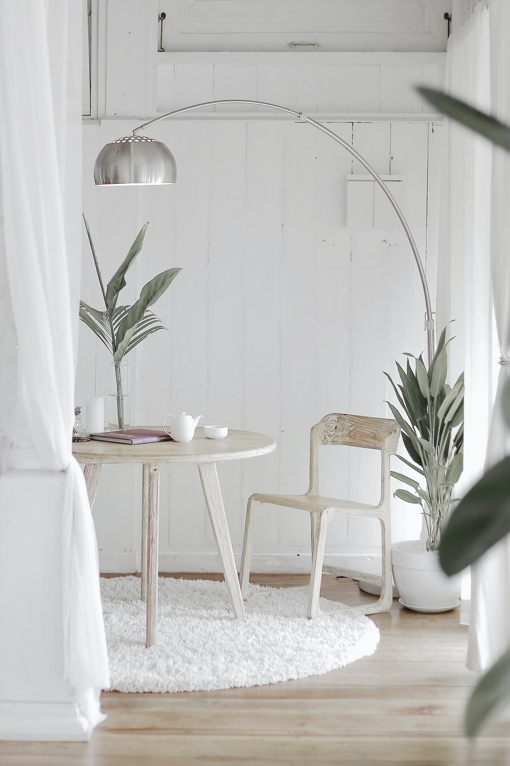 white steel chair in front round table on white rug