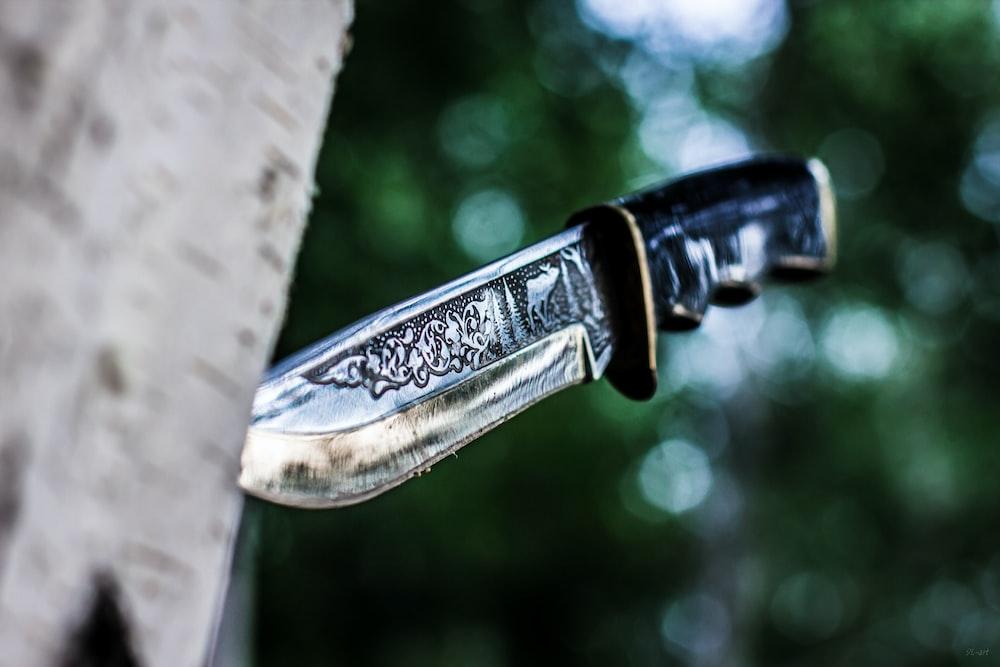 gray metal knife on tree log