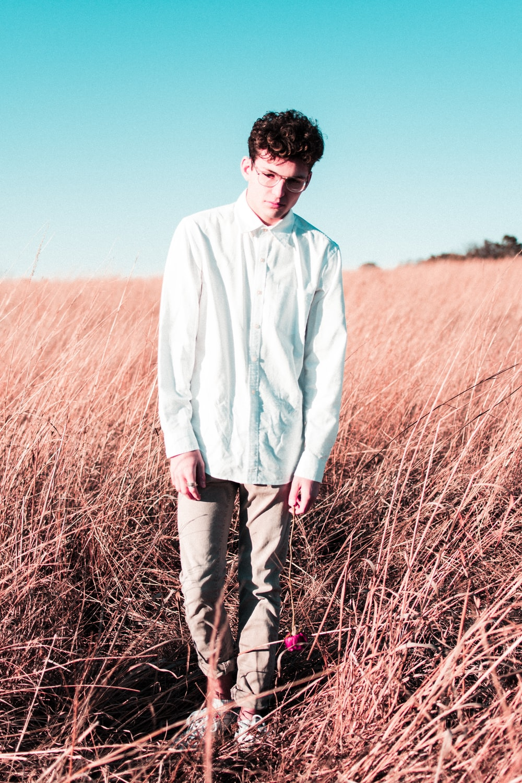 man wearing blue button-up long-sleeved dress shirt on the brown grass