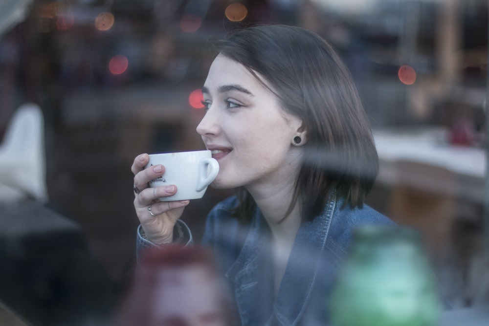 woman holding white ceramic teacup