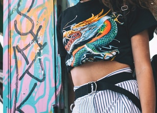 woman wearing dragon graphic t-shirt leaning on door frame
