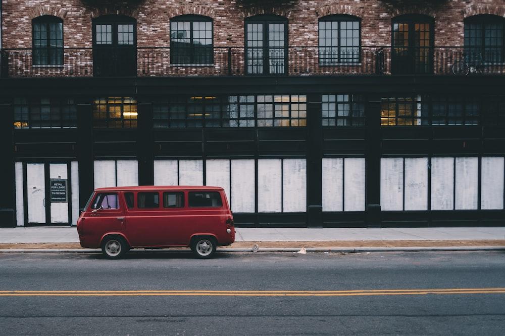 red van on road beside brown concrete house