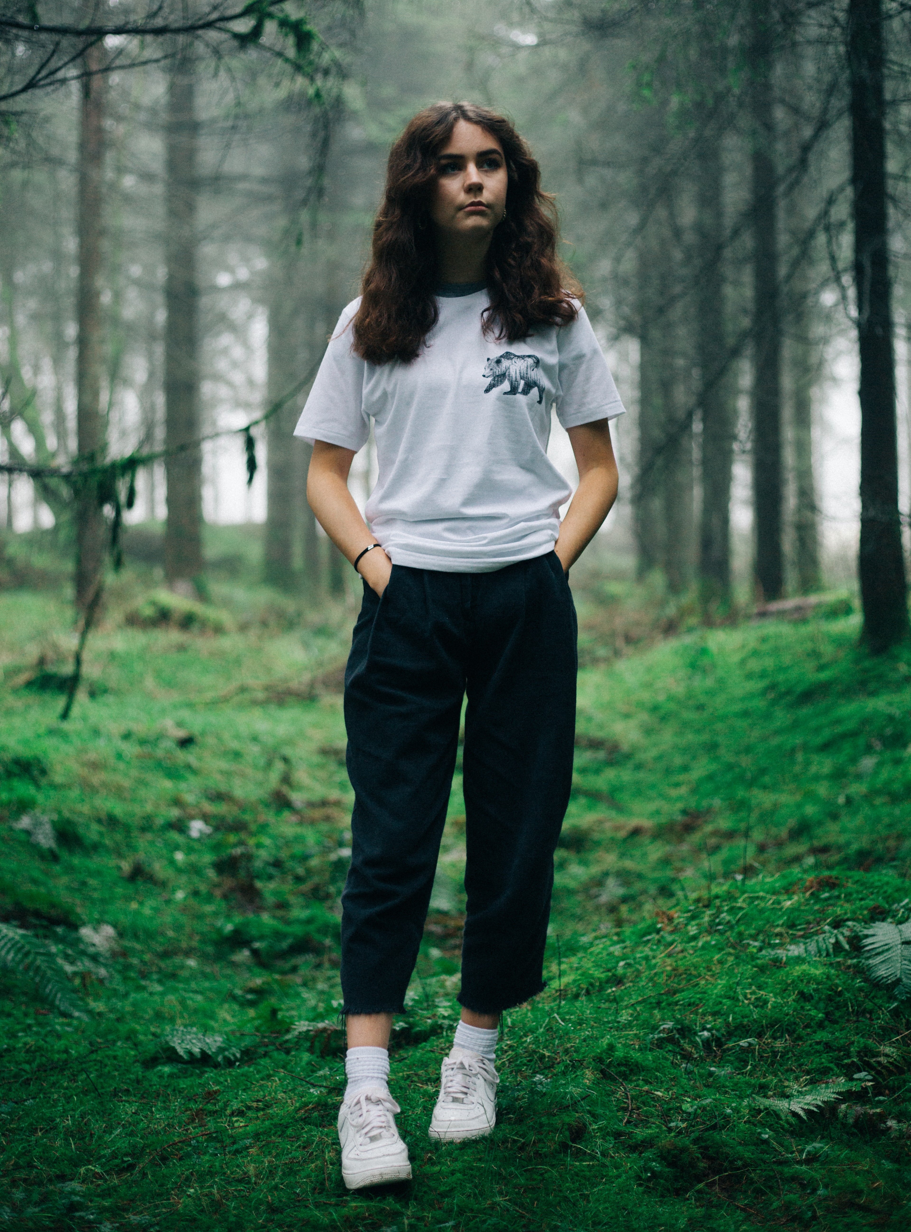 woman standing in middle of forest