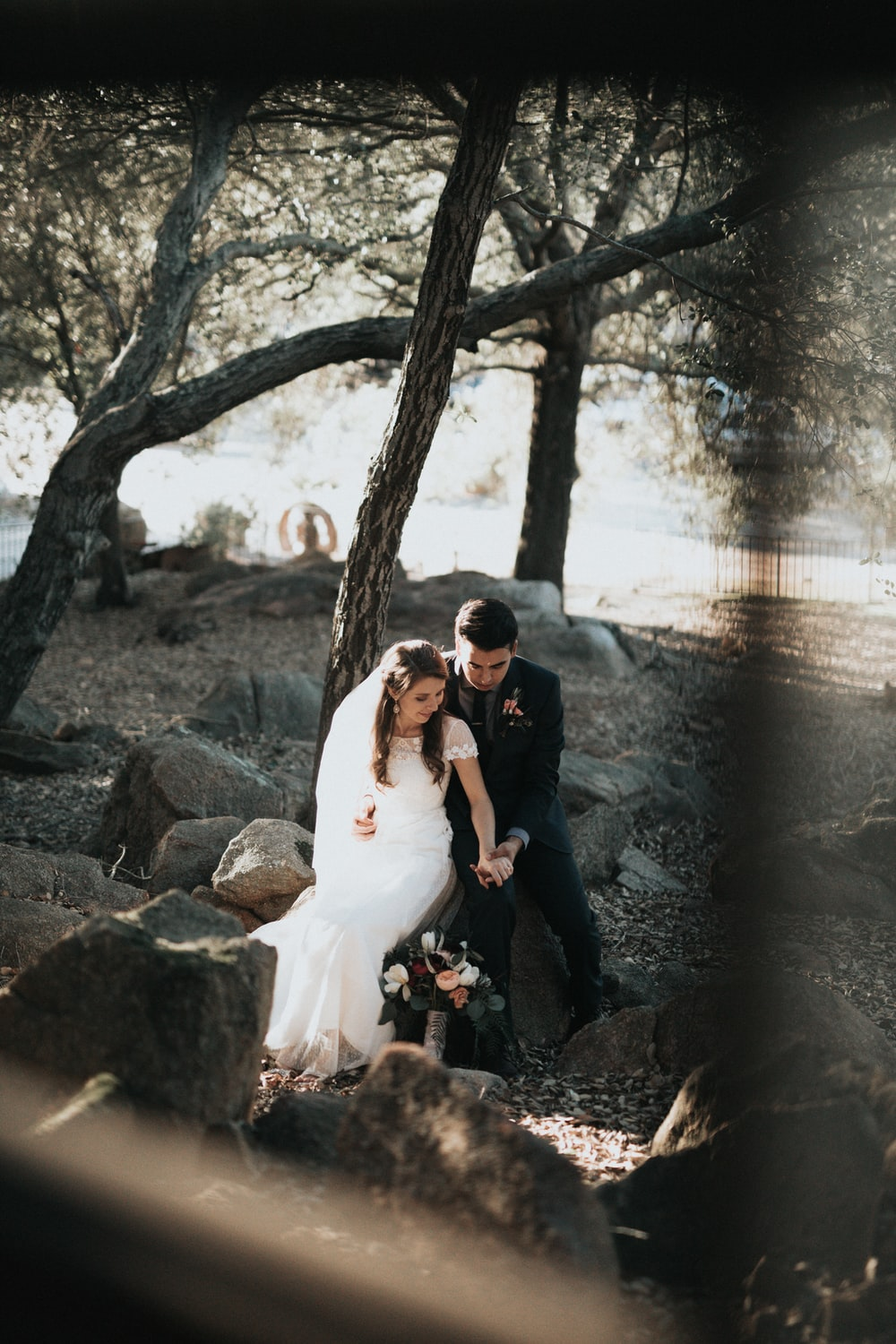 groom and bride sitting on rock holding hands
