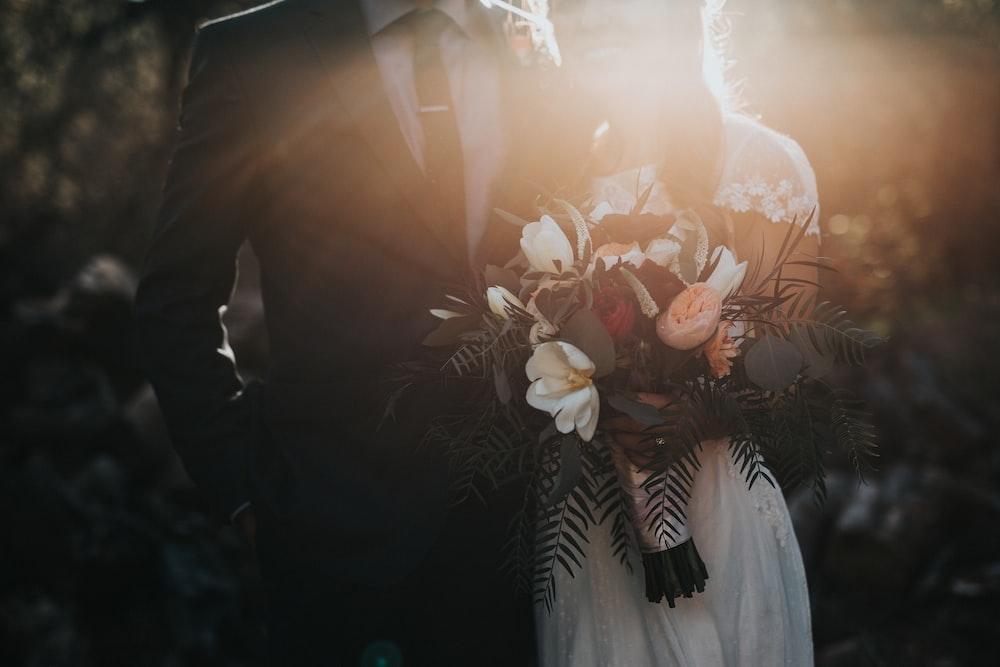 groom beside bride holding bouquet flowers