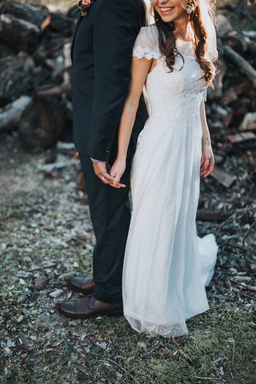 woman wearing white wedding dress holding a man wearing black suit jacket