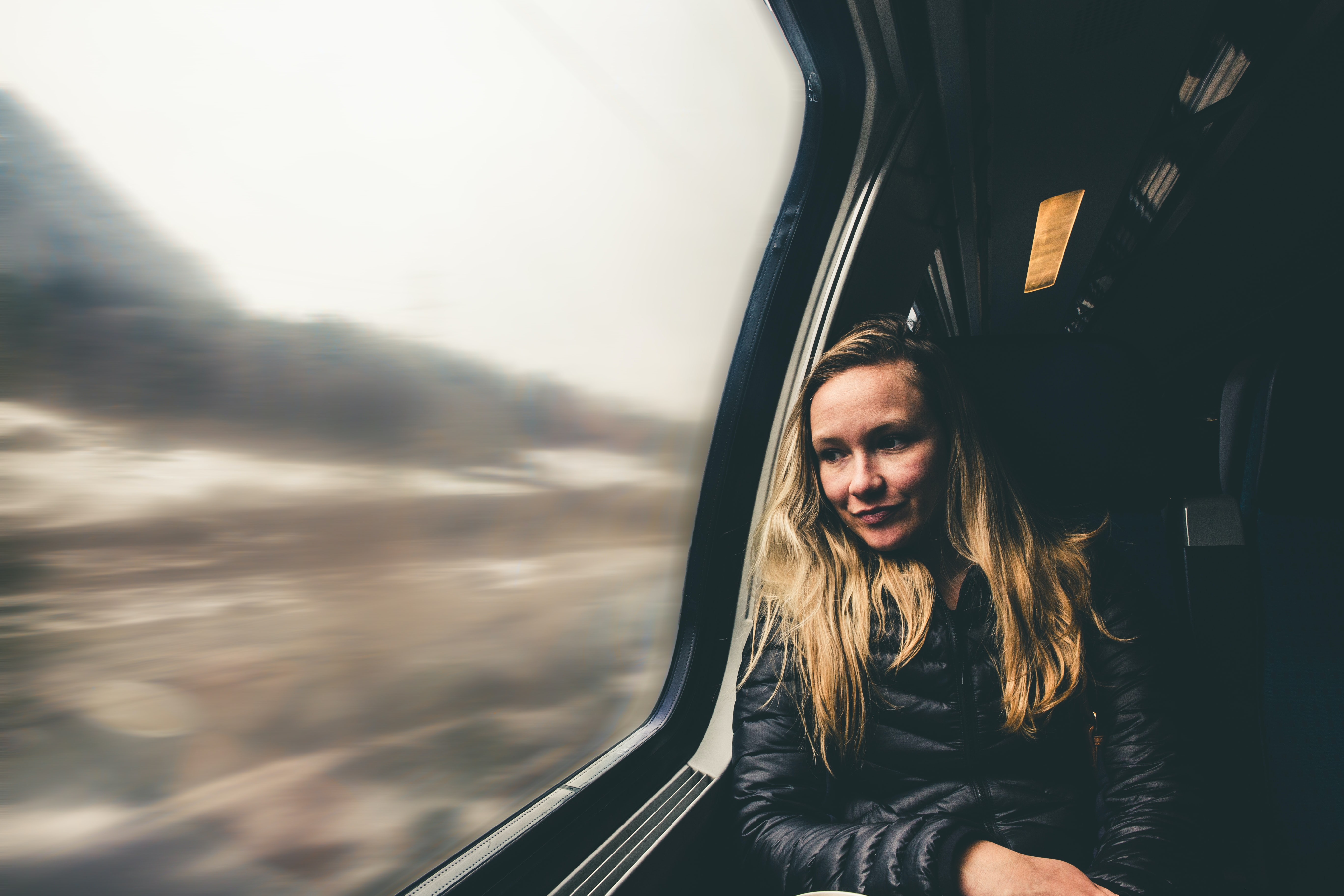 selective focus photography of woman sitting by the window of train