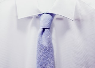 close up photo white collared shirt with blue necktie