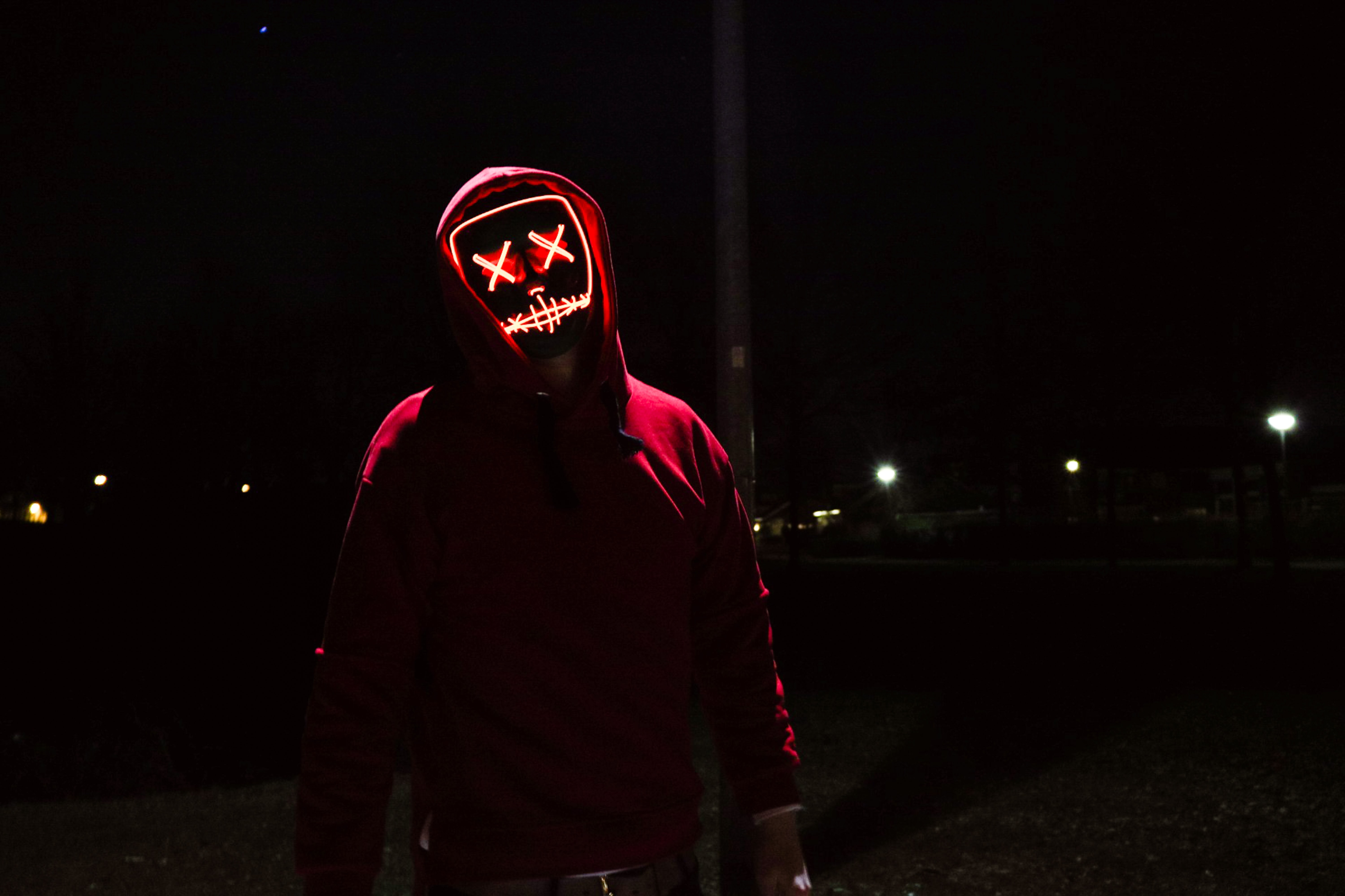 person wearing black mask standing near post