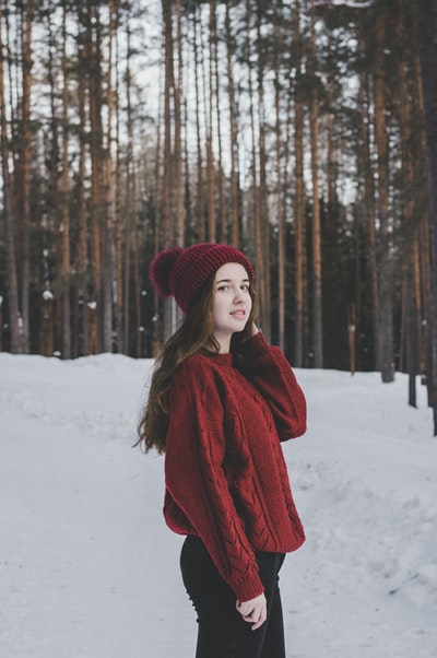 woman standing on snow near forest