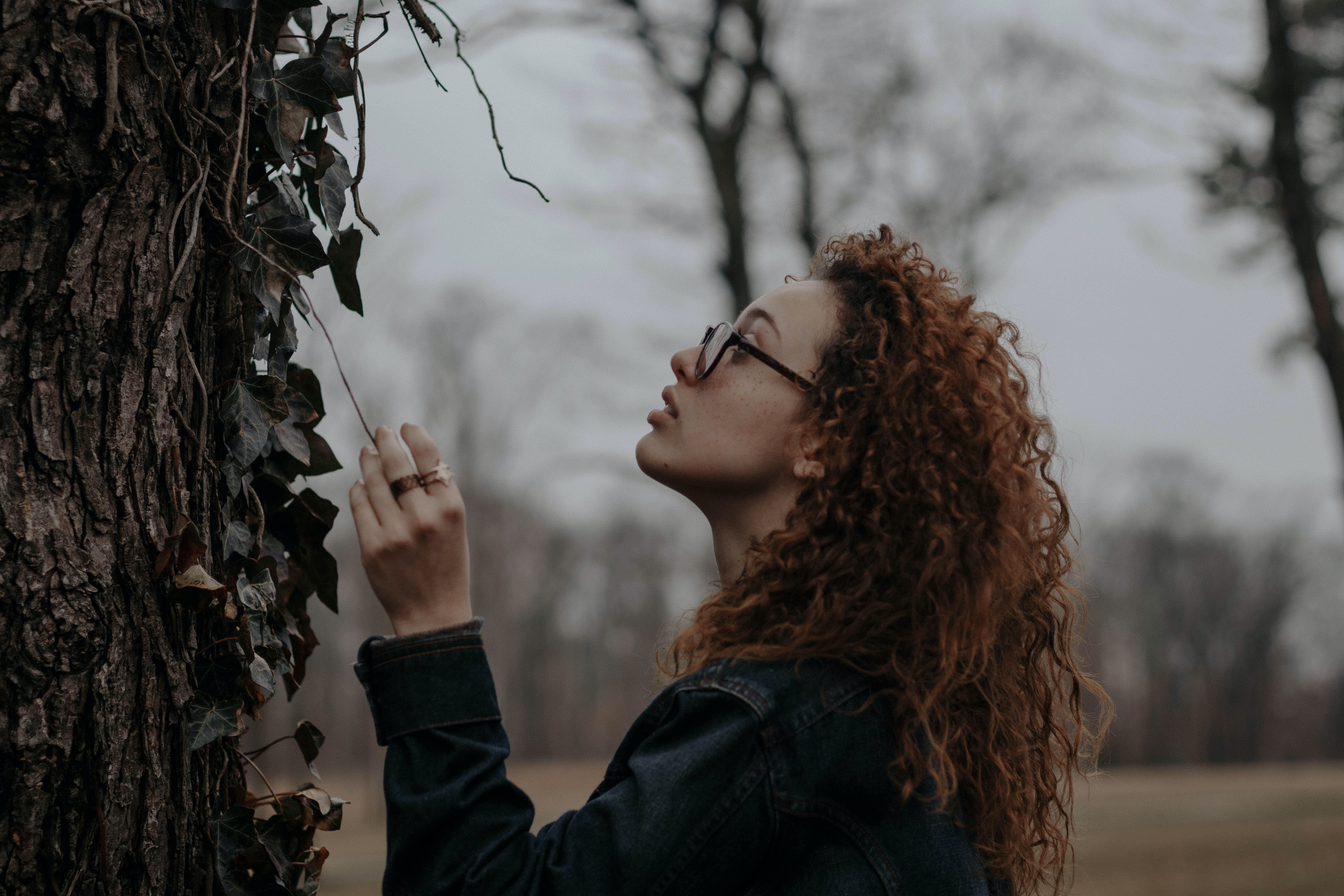 woman holding brown vine of plant near tree
