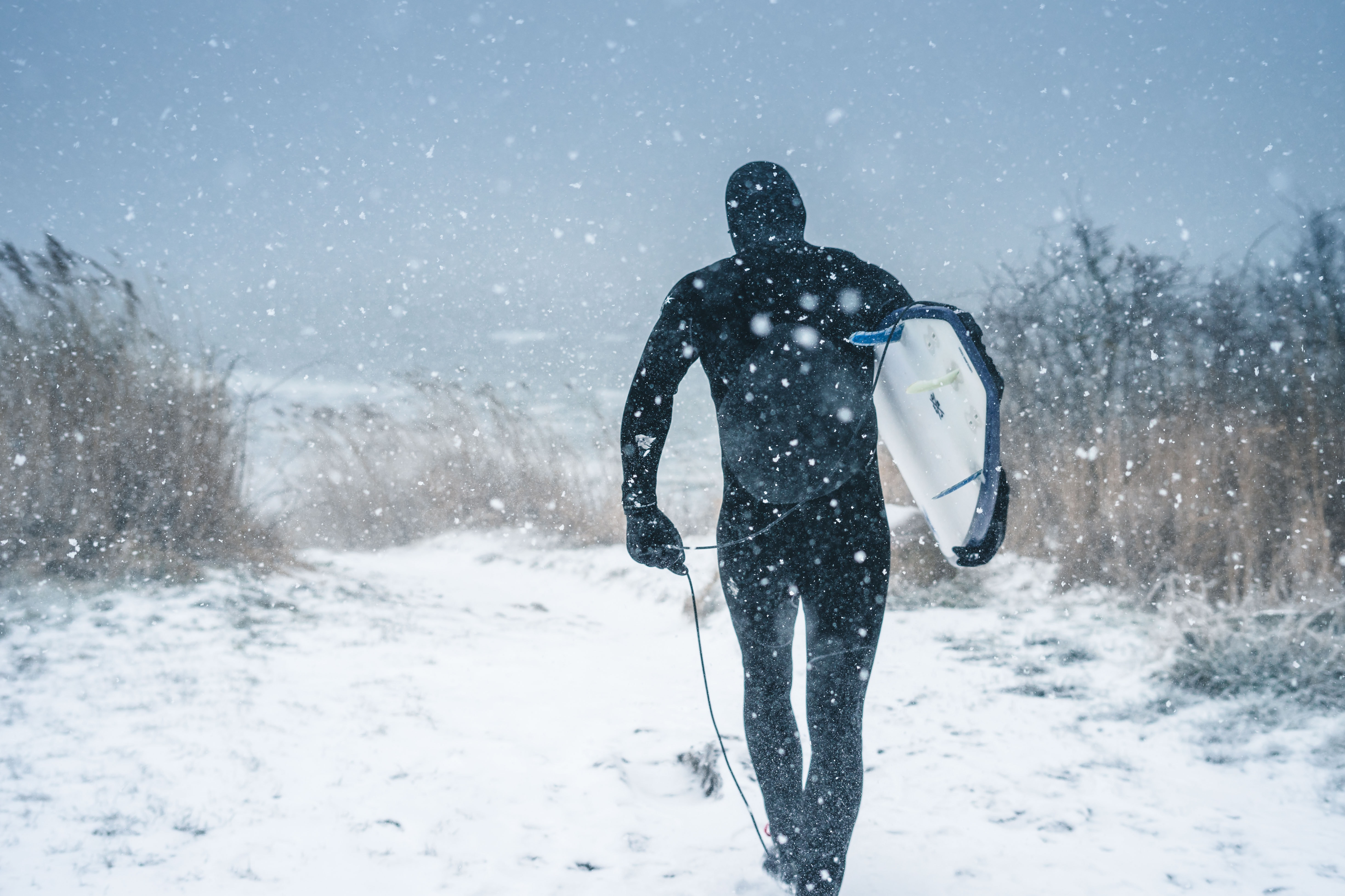 man carrying surfboard walking on snow