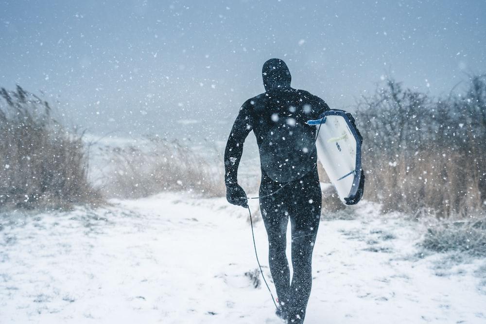 man carrying surfboard walking on snow