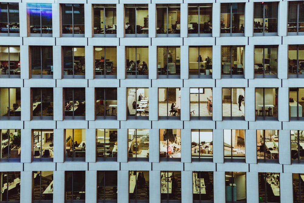 people inside high-rise building with concrete wall