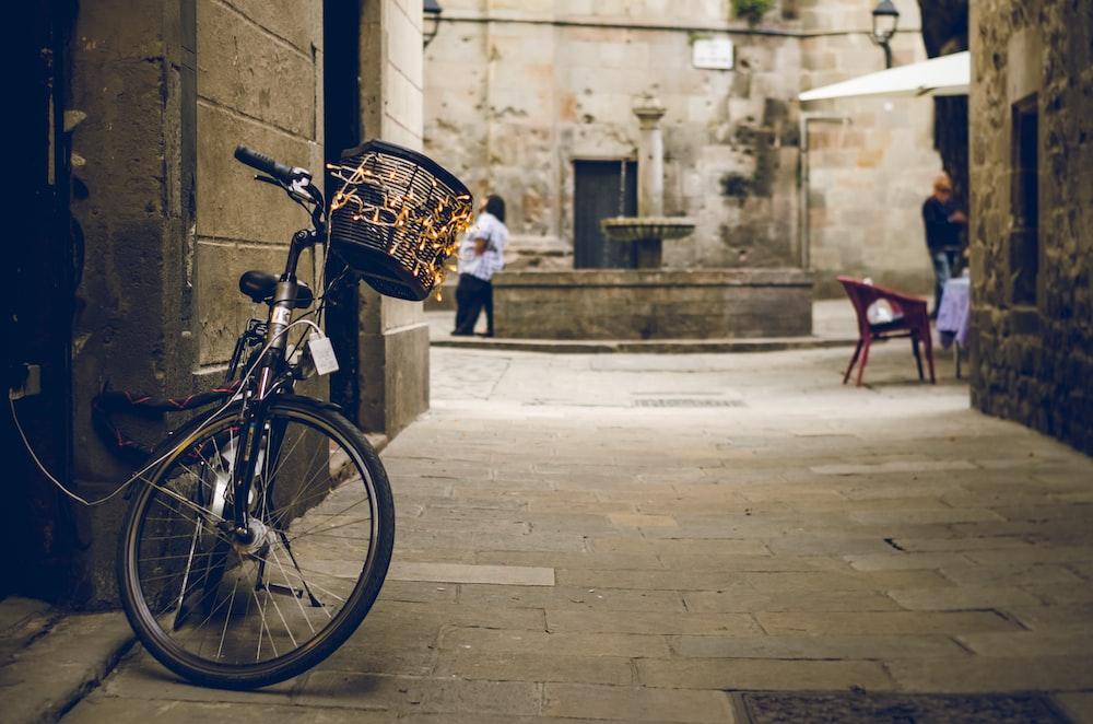 black bicycle beside wooden door