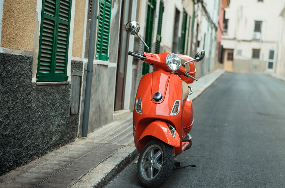 red motor scooter on street during day time