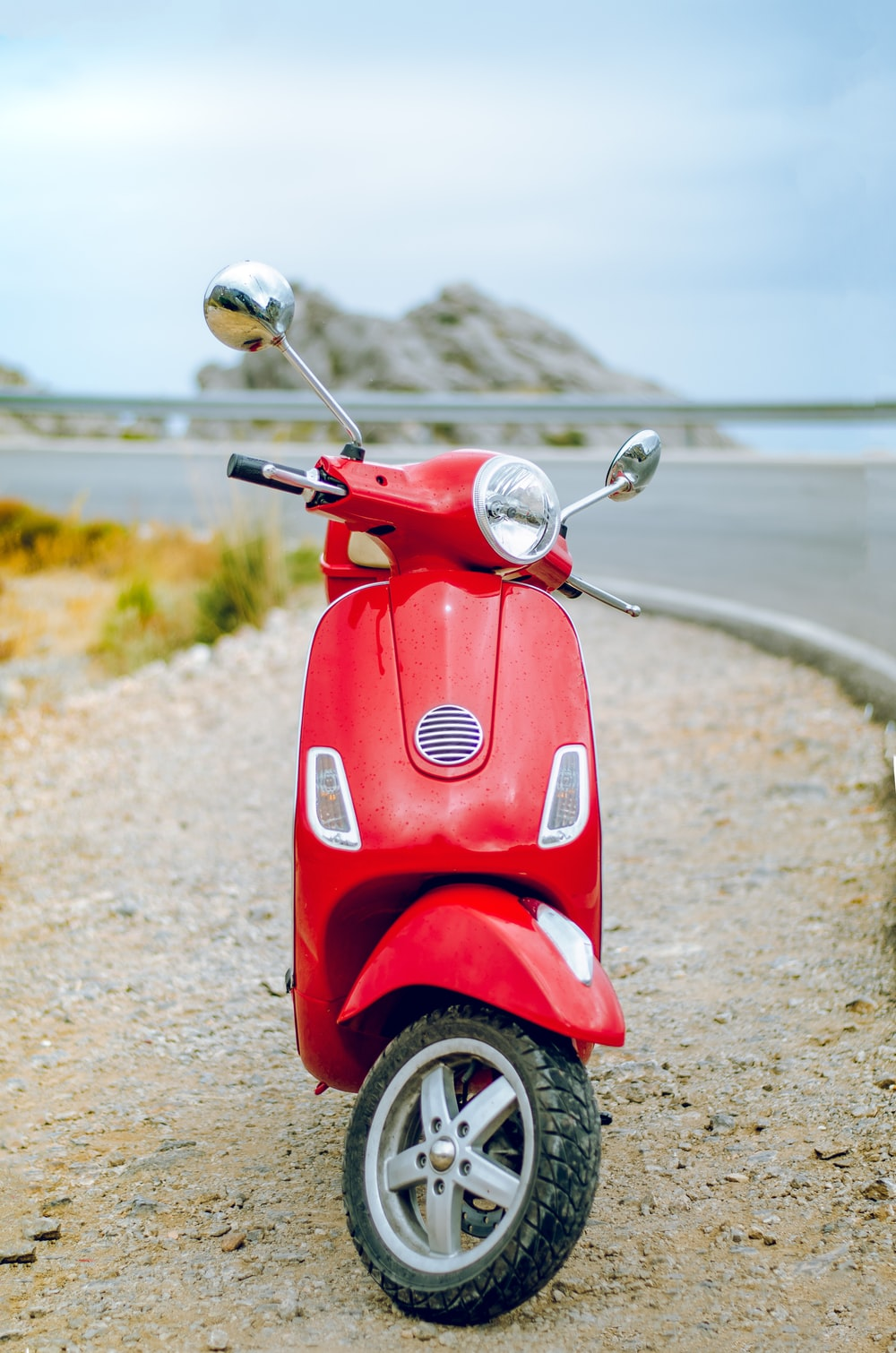 red Vespa motor scooter on side of the road