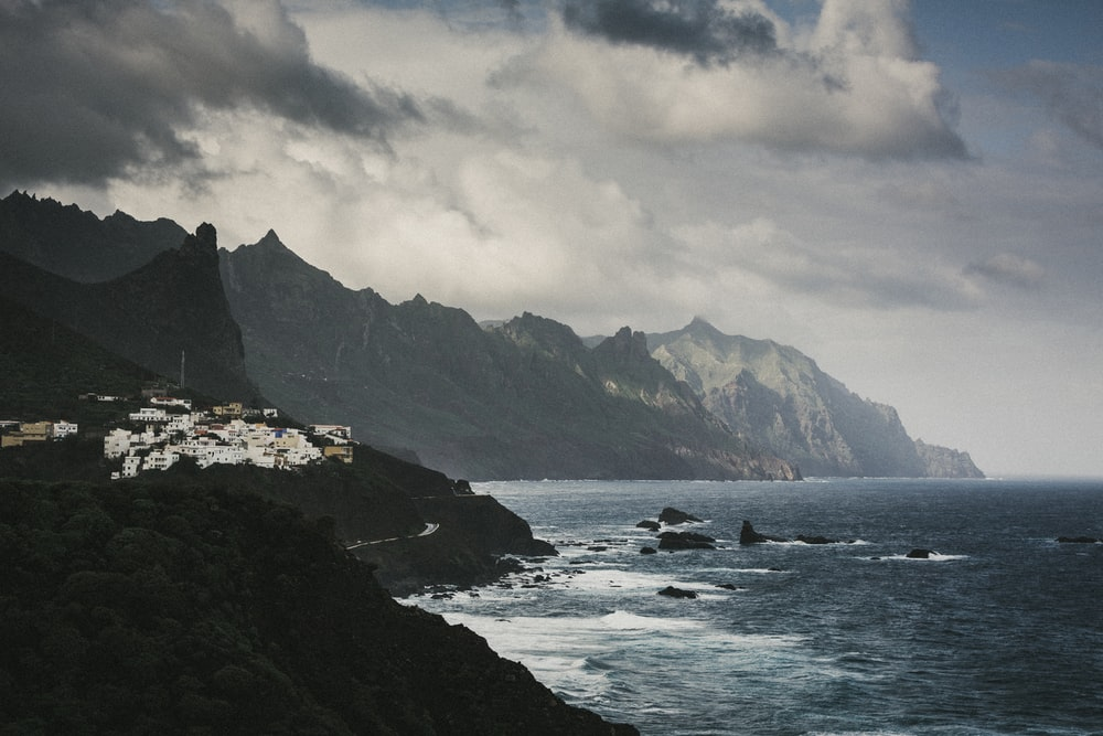 bird's eye view of gray mountain beside body of water