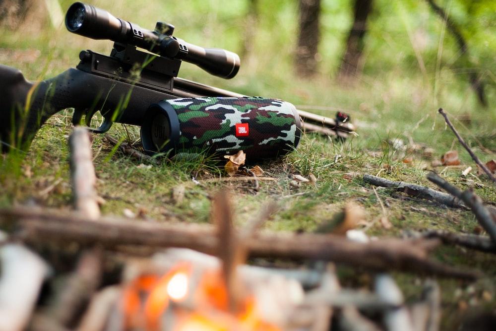black sniper rifle beside green, black, and white camouflage JBL portable speaker