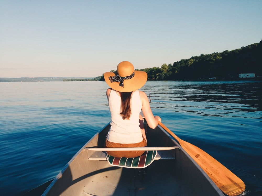 woman wearing sunhat riding boat on body of water