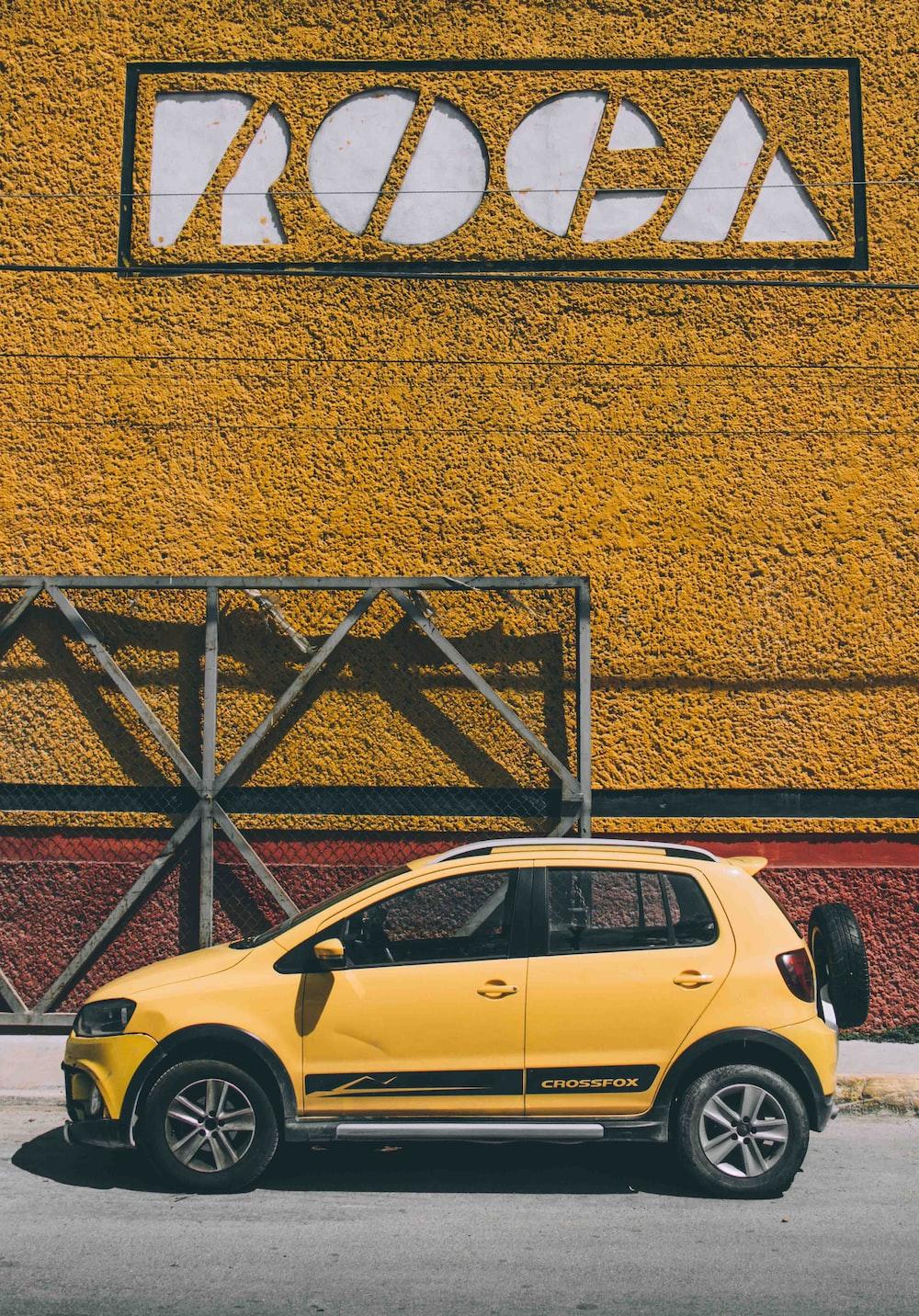 yellow 5-door hatchback parked beside brown metal frame