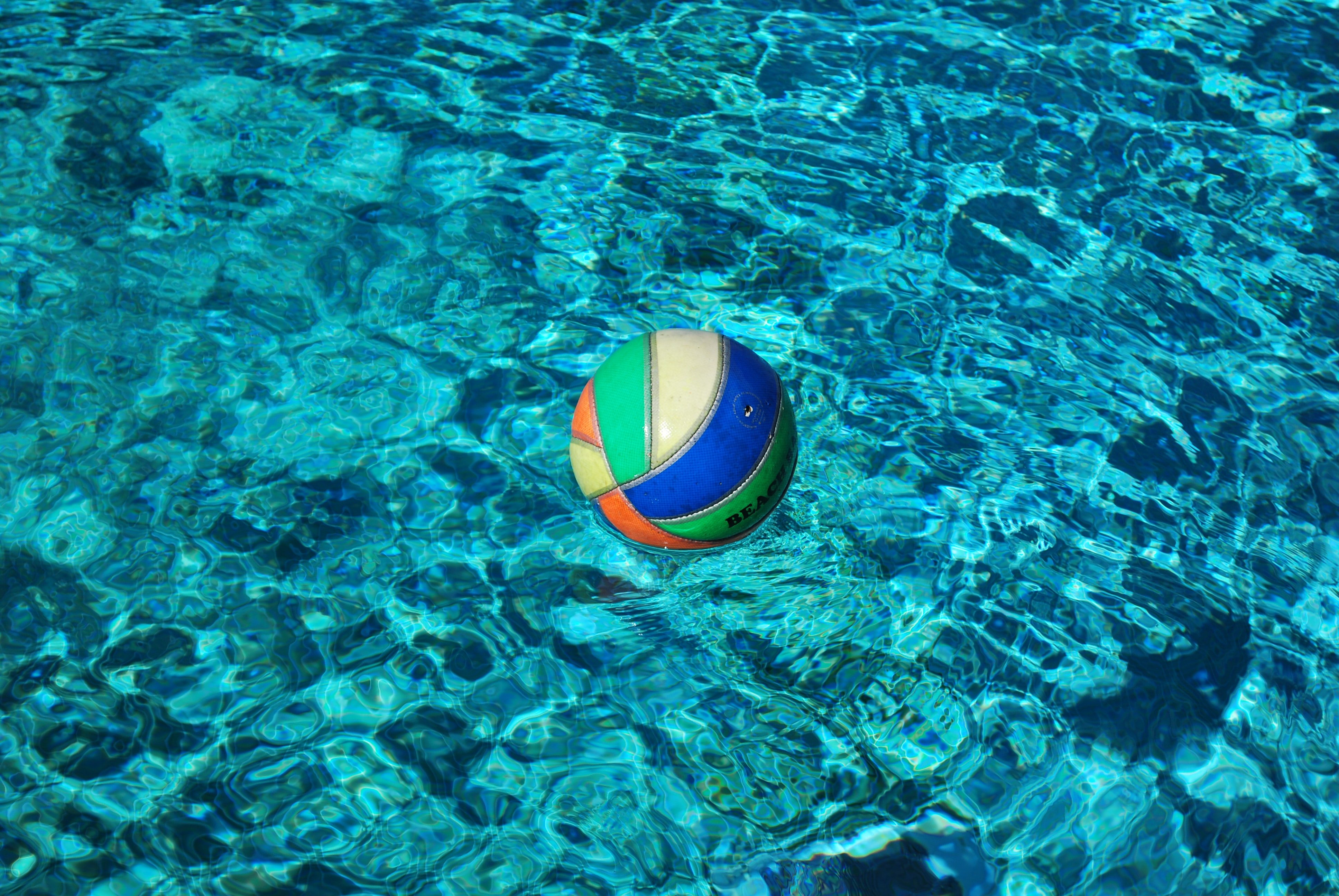 blue and multicolored volley ball on body of water
