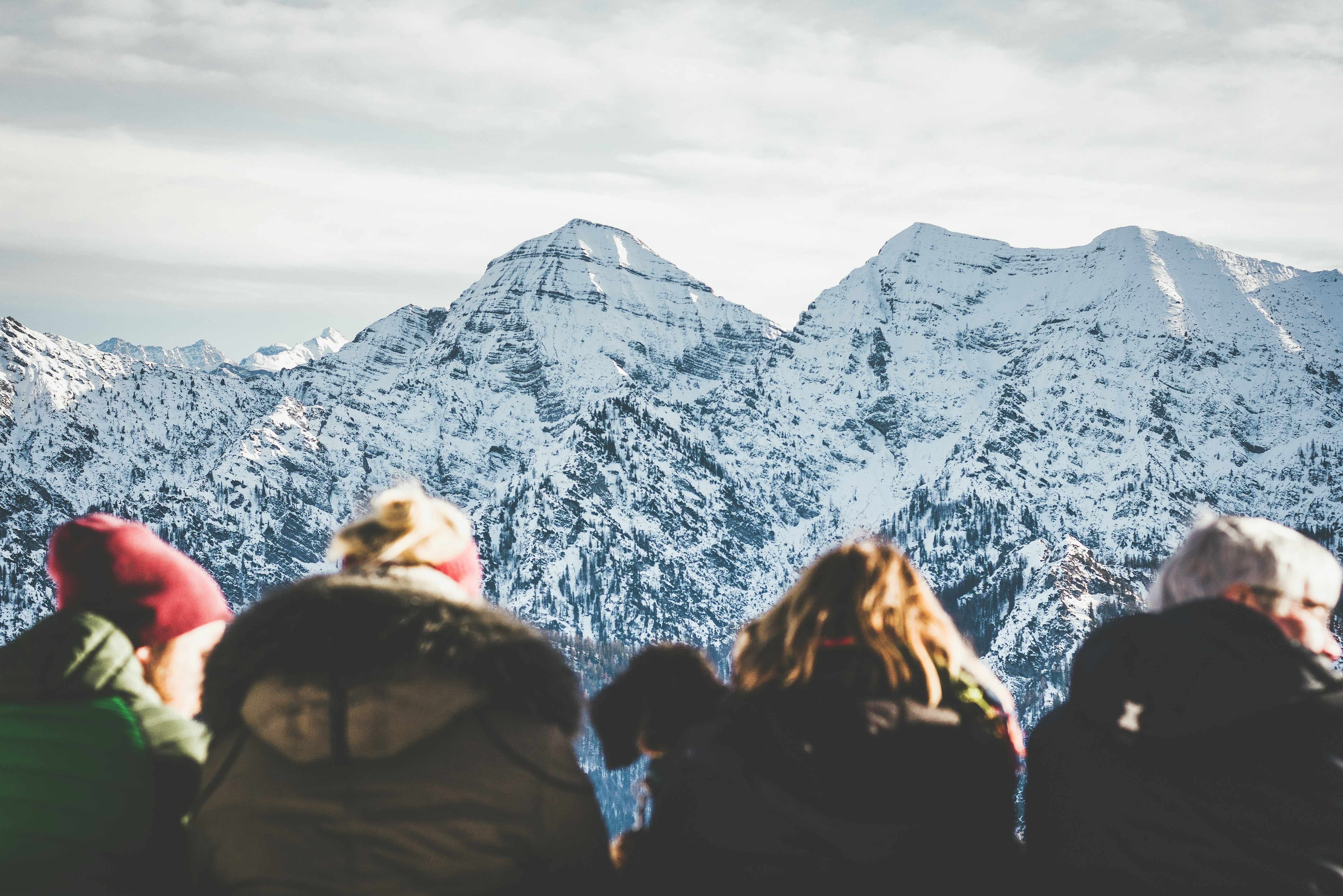 four people viewing snowy mountain during daytime