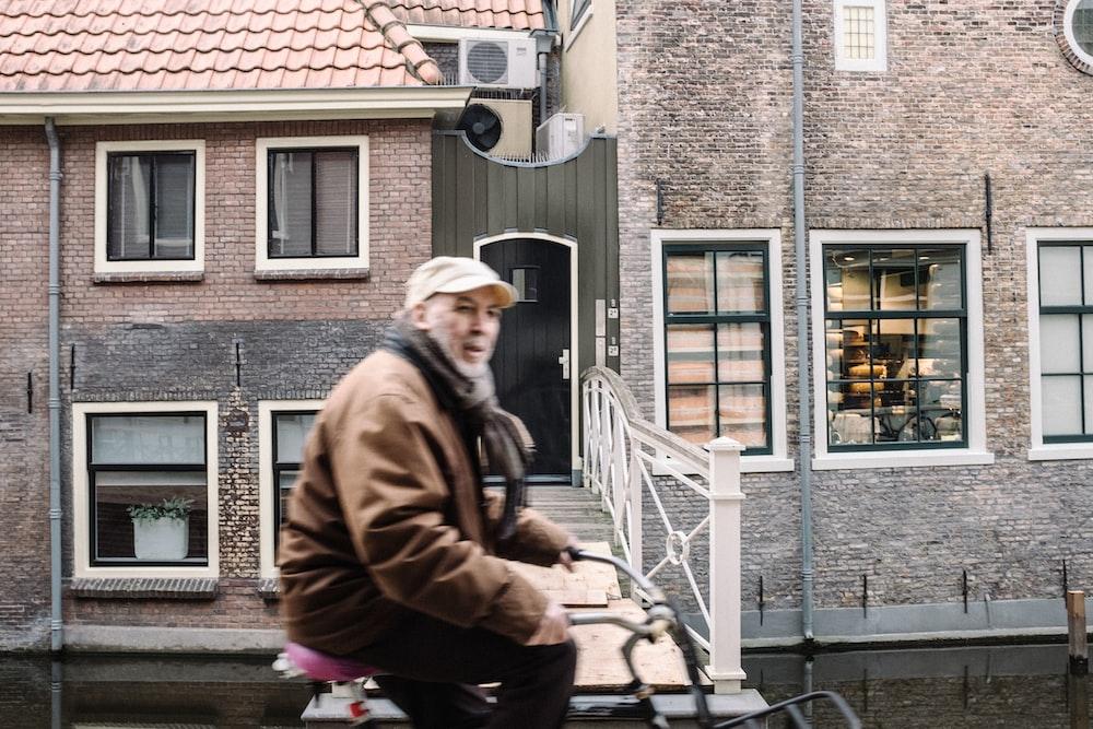 man in brown jacket sitting beside concrete building