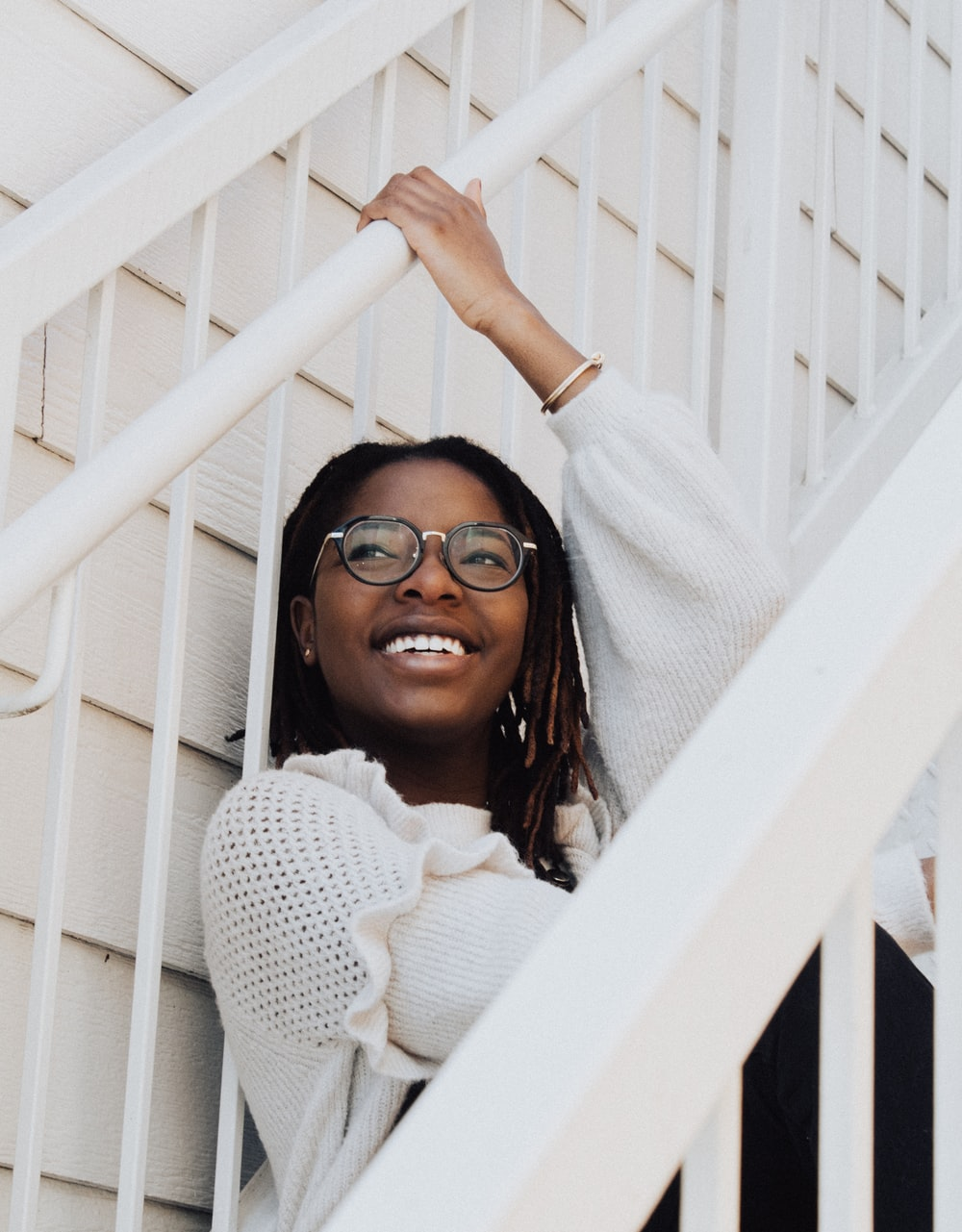 smiling woman sitting on white stairs