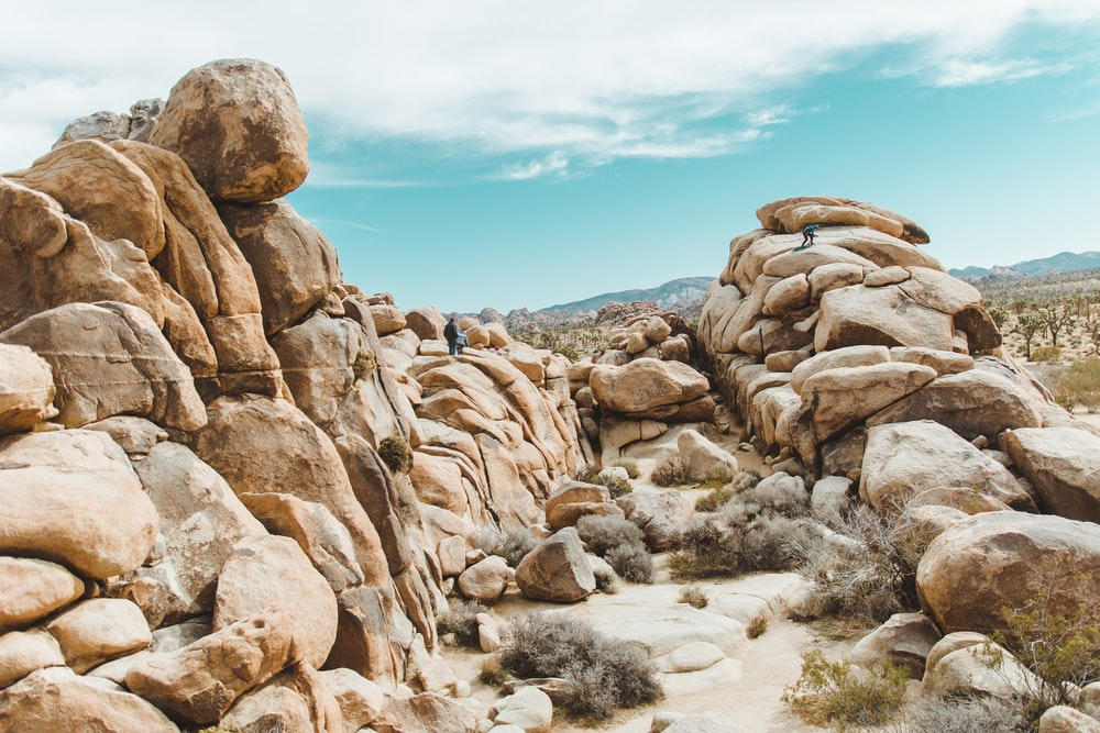 people standing on rock formation under cloudy sky