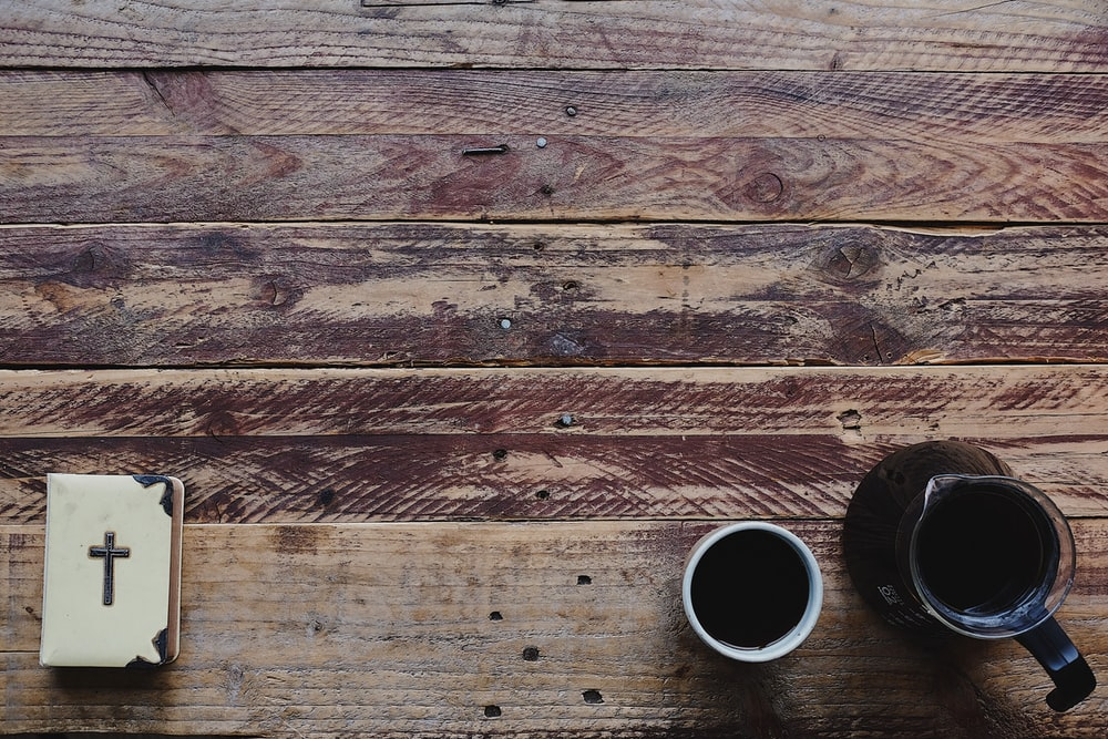 flat-lay photograph of black coffee pot and cup